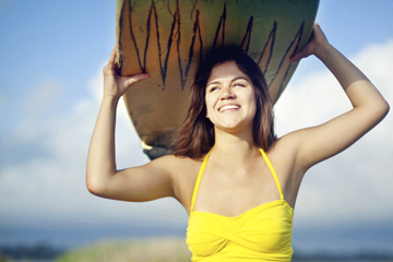 young hispanic woman wearing bright yellow swimsuit sitting on a skateboard in the road smiling while holding surfboard over her head