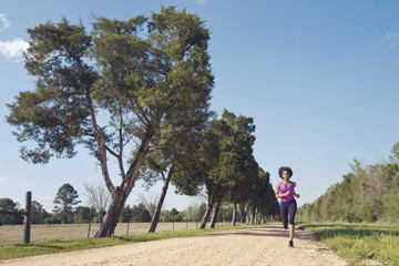 A young woman runs down a rural dirt road lined with evergreen trees.